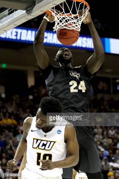 Tacko Fall of the UCF Knights dunks the ball against Vince Williams of the Virginia Commonwealth Rams in the first half during the first round of the...