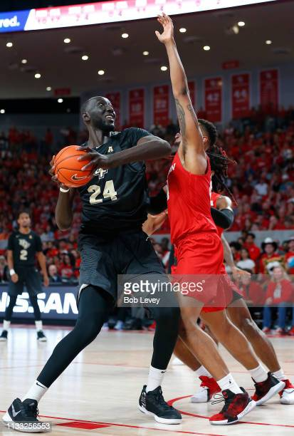 Tacko Fall of the UCF Knights goes up over Breaon Brady of the Houston Cougars and Cedrick Alley Jr #23 during the first half at Fertitta Center on...
