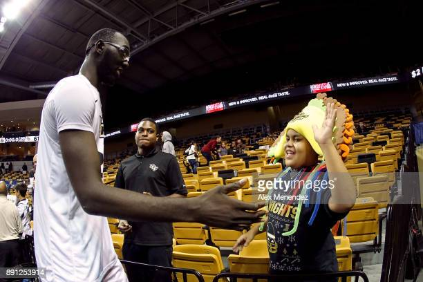 Tacko Fall of the UCF Knights high fives a fan wearing a taco hat after winning a NCAA basketball game against the Southeastern Louisiana Lions at...