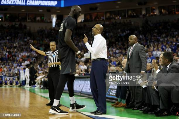 Tacko Fall of the UCF Knights talks with head coach Johnny Dawkins from the bench during the first half in the second round game of the 2019 NCAA...