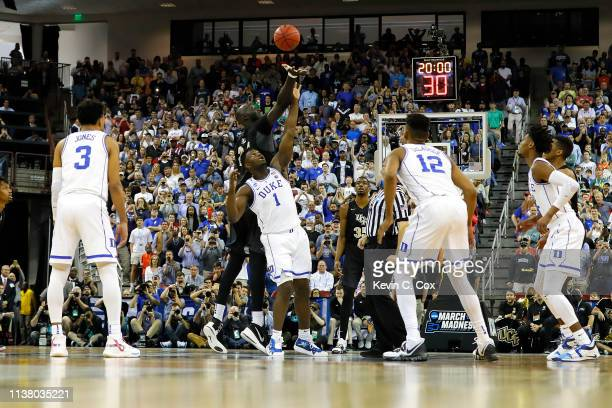 Tacko Fall of the UCF Knights tips off the ball against Zion Williamson of the Duke Blue Devils to start the first half in the second round game of...
