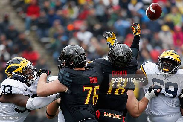 Taco Charlton and Willie Henry of the Michigan Wolverines pressure quarterback Daxx Garman of the Maryland Terrapins duirng the second half of the...