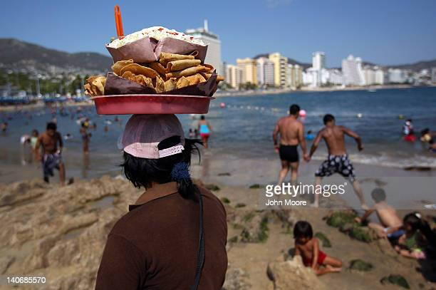A taco vendor scans the beach for clients on March 4 2012 in Acapulco Mexico One of Mexico's top tourist destinations Acapulco has suffered a drop in...