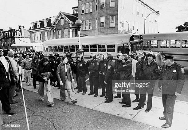 Tactical Patrol Force officers stand guard by school buses carrying black students at South Boston High School on Oct 28 1975 An initiative to...