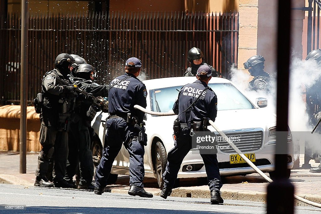 Tactical police use gas canisters and break the drivers side window to remove a man from his vehicle outside NSW Parliament House on Macquarie Street on December 20, 2013 in Sydney, Australia. The NSW Parliament House was locked down due to a security threat outside the building. A man has been apprehended after a stand off with riot police.