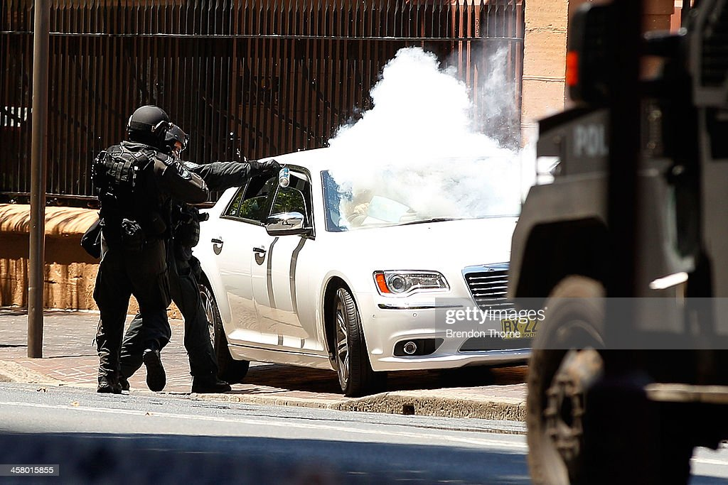Tactical police use gas canisters to remove a man from his vehicle outside NSW Parliament House on Macquarie Street on December 20, 2013 in Sydney, Australia. The NSW Parliament House was locked down due to a security threat outside the building. A man has been apprehended after a stand off with riot police.
