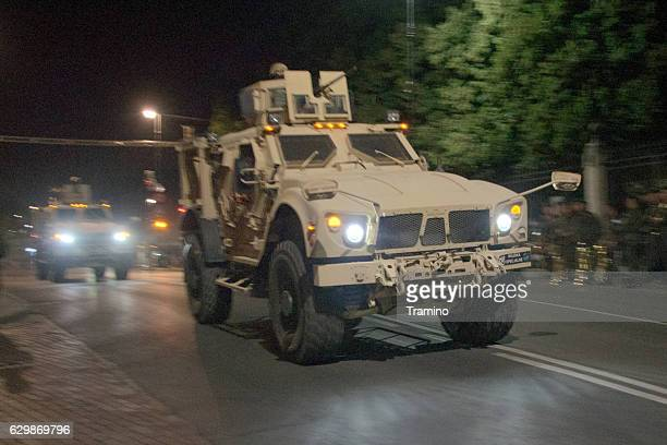 tactical vehicle oshkosh driving on the street at night - mine resistant ambush protected stock pictures, royalty-free photos & images