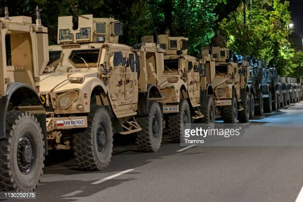 tactical vehicle oshkosh m-atv mrap vehicles parked on the street at night - us army urban warfare stock photos and pictures