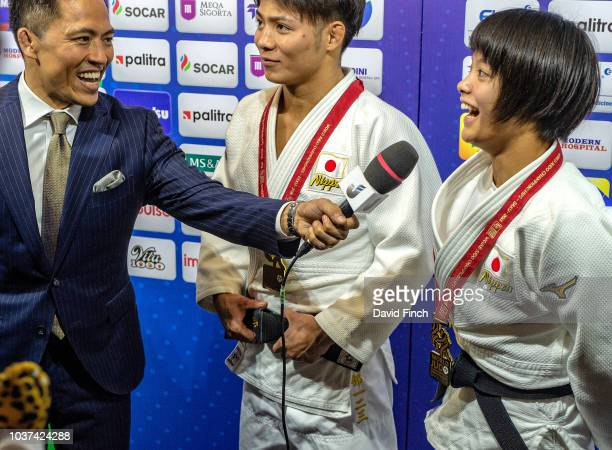 Tadahiro Nomura of Japan jokingly interviews Uta and Hifumi Abe after they uniquely won World gold medals at their weights of u66kg and u52kg during...