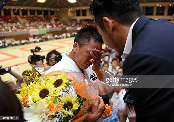 Tadahiro Nomura sheds tears while talking with swimmer Kosuke Kitajima after his defeat in the Men's 60kg third round during the All Japan...