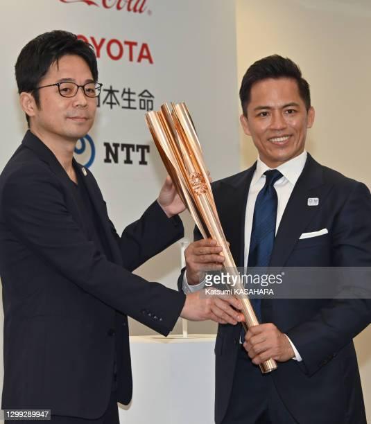 Tadahiro Nomura, triple champion olympique de judo et le designer japonais Tokujin Yoshida montrent le porte flamme olympique de Tokyo 2020 avec un...