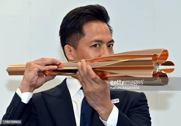 Tadahiro Nomura, triple champion olympique de judo montre le porte flamme olympique de Tokyo 2020 avec un motif de pétales de fleurs de cerisier lors...
