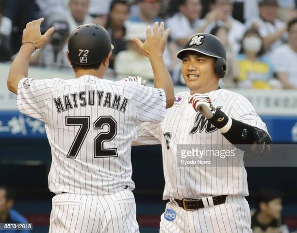 Tadahito Iguchi of the Lotte Marines is greeted by infield and running coach Hideaki Matsuyama after hitting a gametying tworun homer in the ninth...