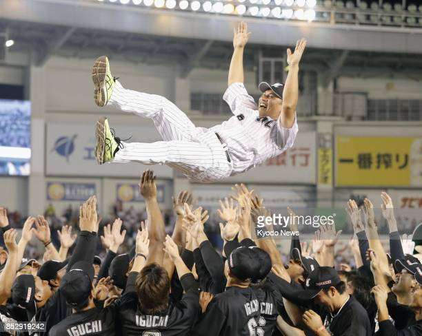 Tadahito Iguchi of the Lotte Marines is tossed into the air after playing in the last game of his career at Zozo Marine Stadium in Chiba Japan on...
