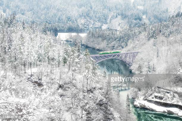tadami line train run on first bridge across tadami river in winter, fukushima, japan - land feature stock pictures, royalty-free photos & images
