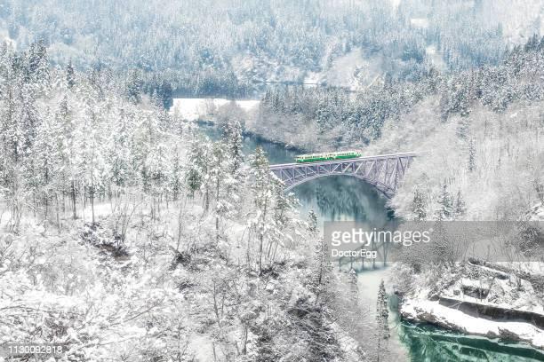 tadami line train run on first bridge across tadami river in winter, fukushima, japan - 六月 ストックフォトと画像