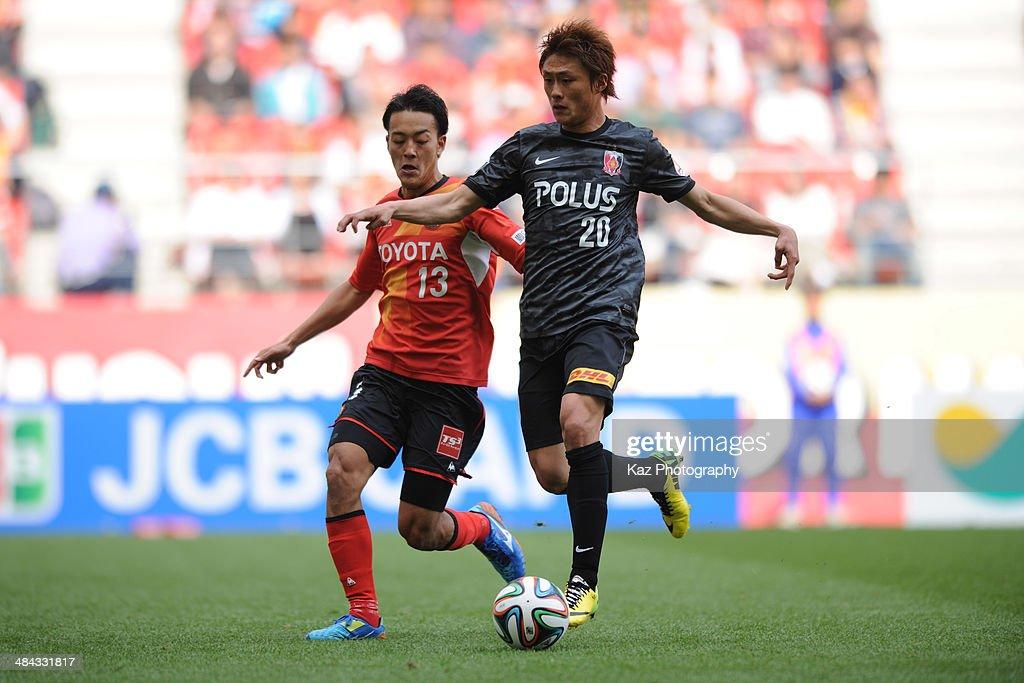 Tadanari Lee (R) of Urawa Red Diamonds dribbles the ball under the pressure from Ryota Isomura of Nagoya Grampus during the J. League match between Nagoya Grampus and Urawa Red Diamonds at the Toyota Stadium on April 12, 2014 in Toyota, Japan.