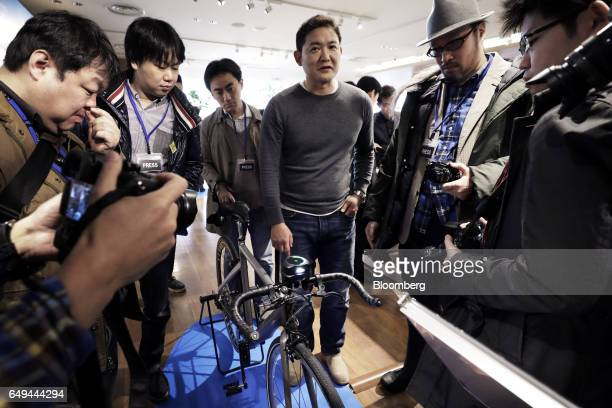 Tadashi Aoyagi director of Japan at Blue Green Group Inc third from right explains a CycleLabs Solutions Inc SmartHalo smart biking device to...