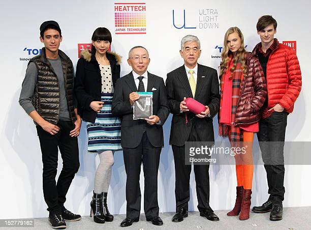 Tadashi Yanai chairman president and chief executive officer of Fast Retailing Co center left and Akihiro Nikkaku president and chief executive...