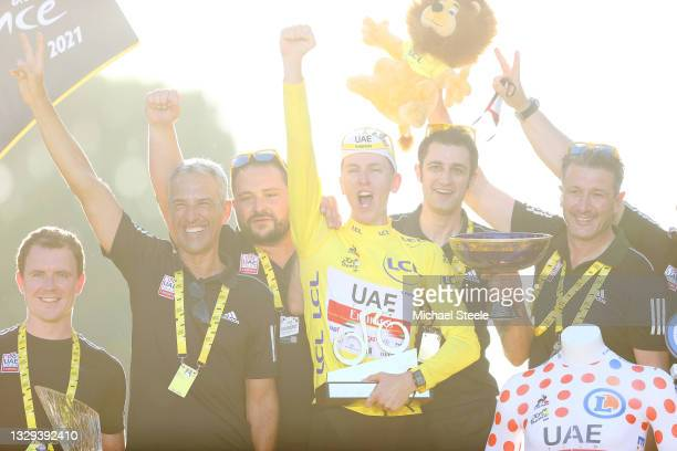 Tadej Pogačar of Slovenia and UAE-Team Emirates Yellow Leader Jersey and staff members celebrate at podium during the 108th Tour de France 2021,...