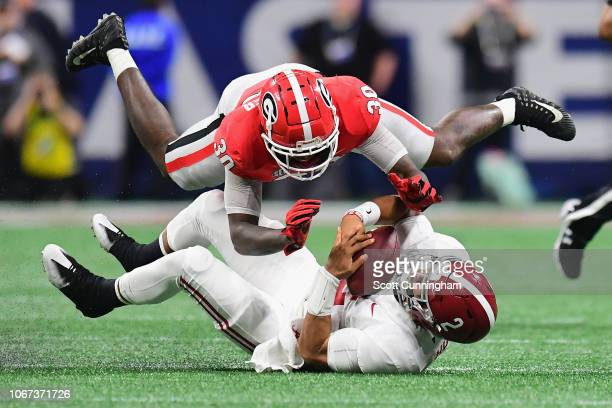 Tae Crowder of the Georgia Bulldogs tackles Jalen Hurts of the Alabama Crimson Tide in the second half during the 2018 SEC Championship Game at...