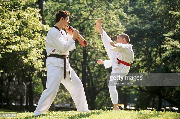 tae kwon do master instructing boy (9-11) in park, profile - martial arts stock pictures, royalty-free photos & images
