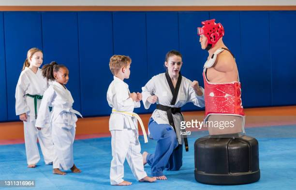 taekwondo teacher and students practice on dummy - martial arts stock pictures, royalty-free photos & images