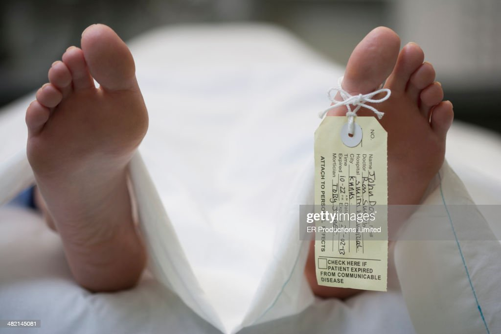 Tag on foot of Caucasian body on gurney : Stock Photo