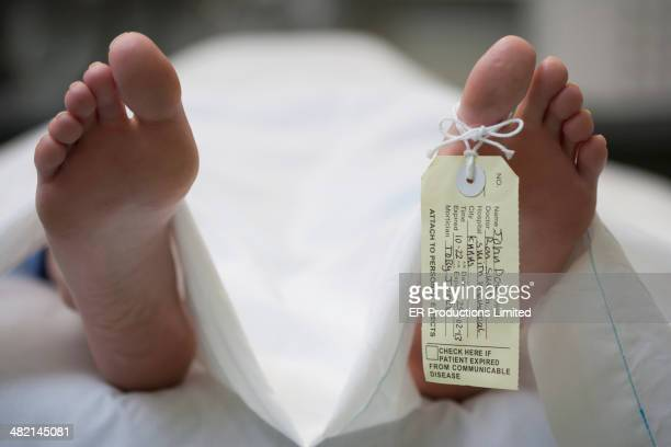 tag on foot of caucasian body on gurney - dead body stockfoto's en -beelden