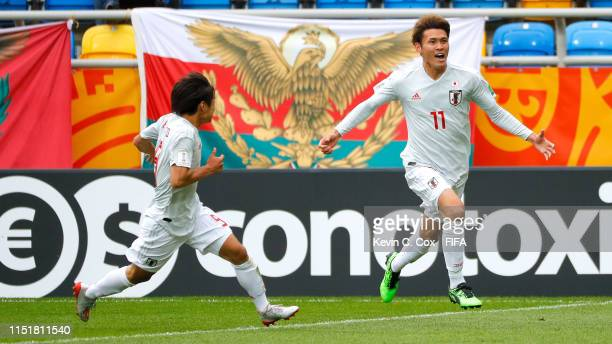 Tagawa of Japan celebrates with his team mate Saito after scoring his team's second goal during the 2019 FIFA U-20 World Cup group B match between...