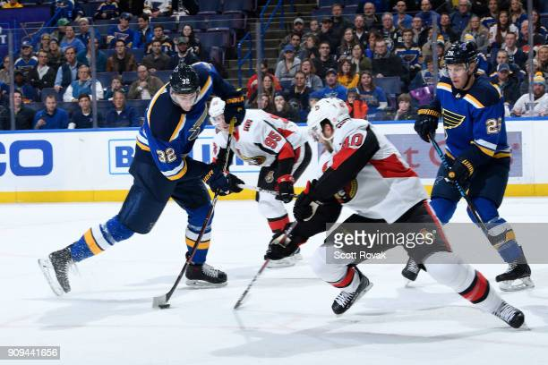 Tage Thompson of the St Louis Blues takes a shot as Gabriel Dumont of the Ottawa Senators defends at Scottrade Center on January 23 2018 in St Louis...