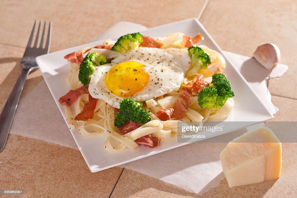 Tagliatelle pasta with broccoli, prosciutto and fried egg. : Stock Photo