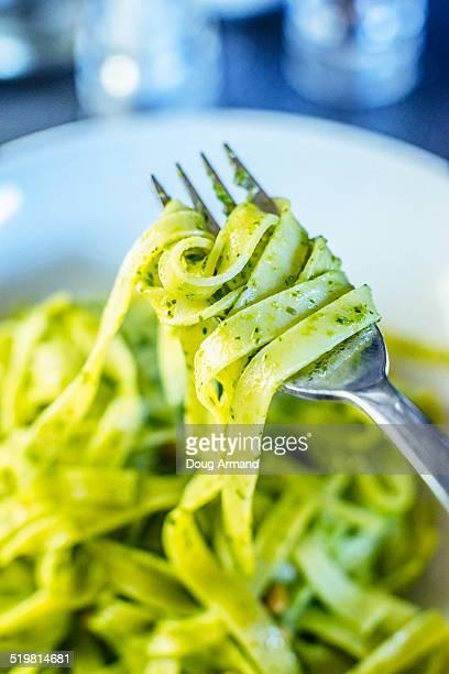 Tagliatelle pasta with Green Pesto sauce on a silv