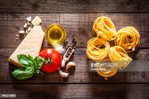 Tagliatelle pasta with ingredients on rustic wooden table