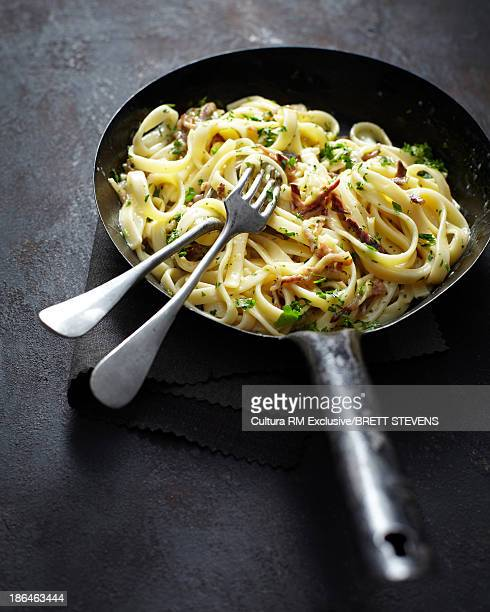 Tagliatelle with bacon and parsley in frying pan