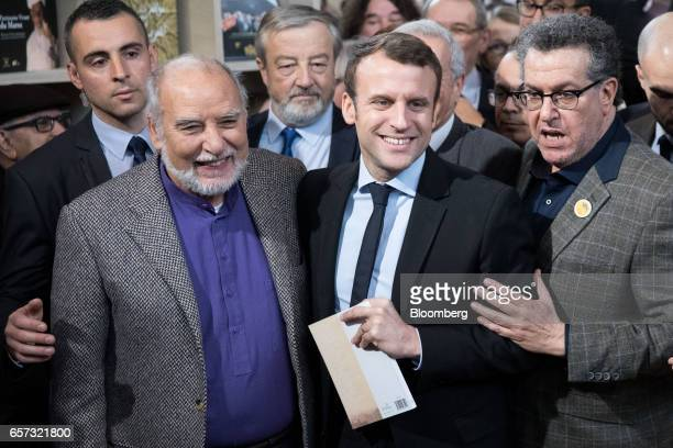 Tahar Ben Jelloun writer left poses for a photograph with Emmanuel Macron France's independent presidential candidate as he visits the Salon du Livre...