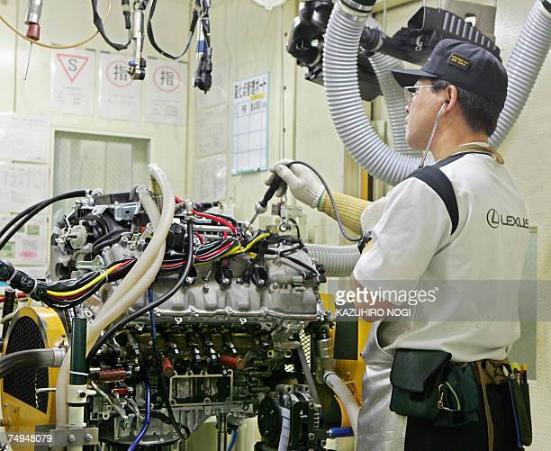 A worker at Japan's auto giant Toyota motor takes final inspection of engine sound using auditory sense for LEXUS cars at the company's Tahara plant...