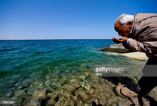 Taher an engineer drinks water from an artificial lake created on the site of the Great Man Made River in May 2000 in Surt Libya