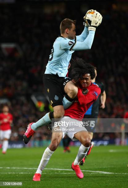 Tahith Chong of Manchester United collides with Simon Mignolet of Club Brugge during the UEFA Europa League round of 32 second leg match between...