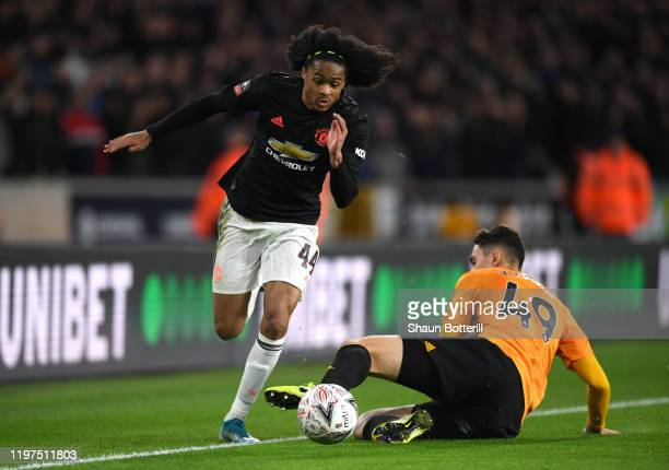 Tahith Chong of Manchester United is tackled by Max Kilman of Wolverhampton Wanderers during the FA Cup Third Round match between Wolverhampton...