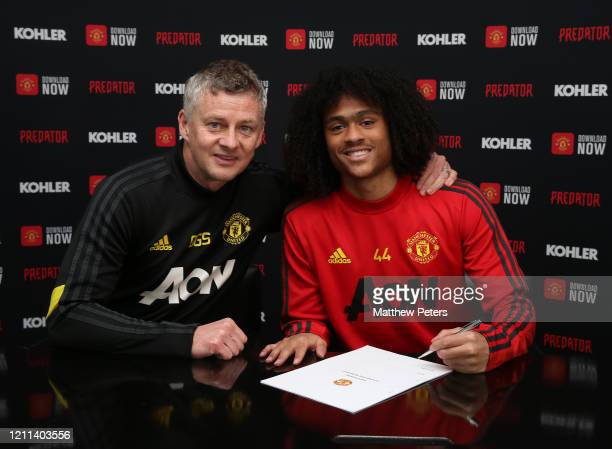 Tahith Chong of Manchester United poses with Manager Ole Gunnar Solskjaer after signing a new contract with Manchester United at Aon Training Complex...