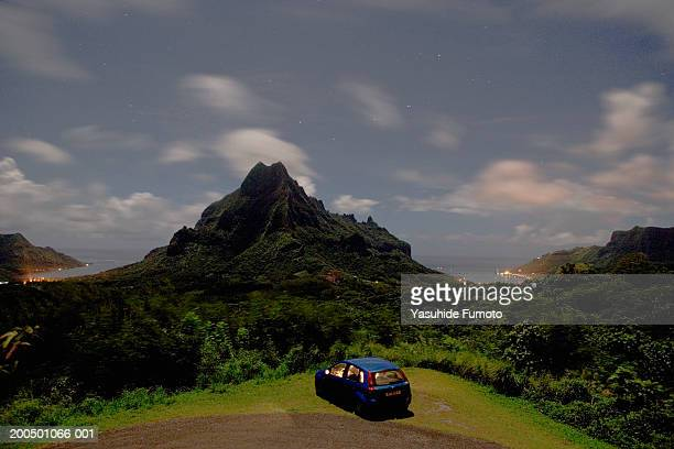 Tahiti, car overlooking lush mountains at dusk, elevated view