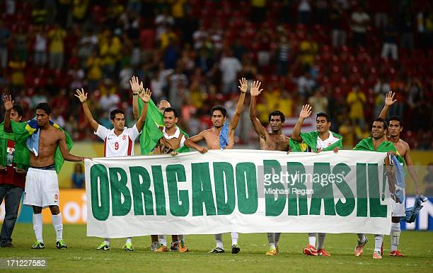 """Tahiti holds up a sign reading """"Obrigado Brasil"""" after the FIFA Confederations Cup Brazil 2013 Group B match between Uruguay and Tahiti at Arena..."""