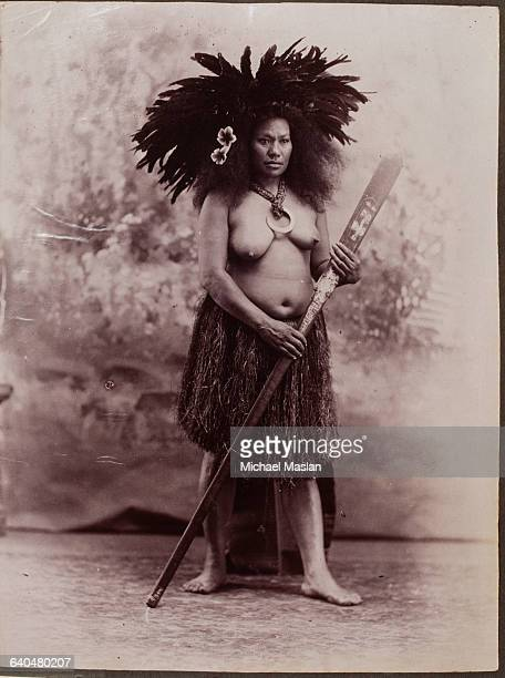 A Tahitian woman stands in front of a painted backdrop holding a carved stick She is wearing a grass skirt a large headdress made of feathers and a...