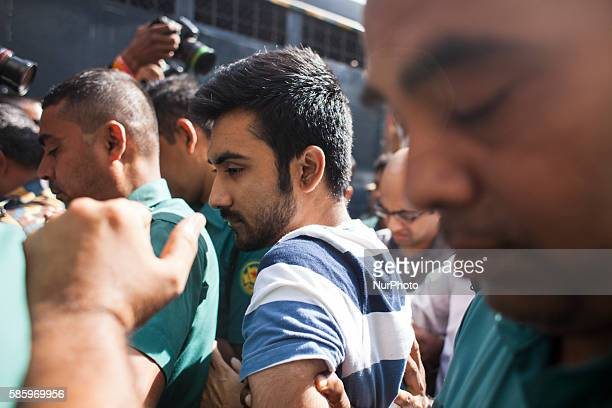 Tahmid Khan a student at the University of Toronto in connection with a deadly siege in a cafe in Dhaka last month are surrounded by police officers...