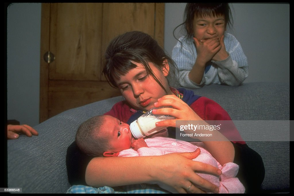 Tai Li feeding adopted sister Angelina as younger (adopted) sister Chere looks on, re Amer. photograher Forrest Anderson & wife Donna's adoption of Chinese orphan(s).
