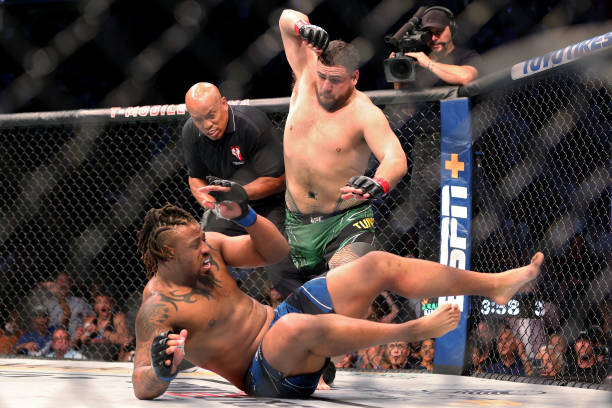 Tai Tuivasa of Australia takes down Greg Hardy in the first round in their heavyweight bout during UFC 264: Poirier v McGregor 3 at T-Mobile Arena on...
