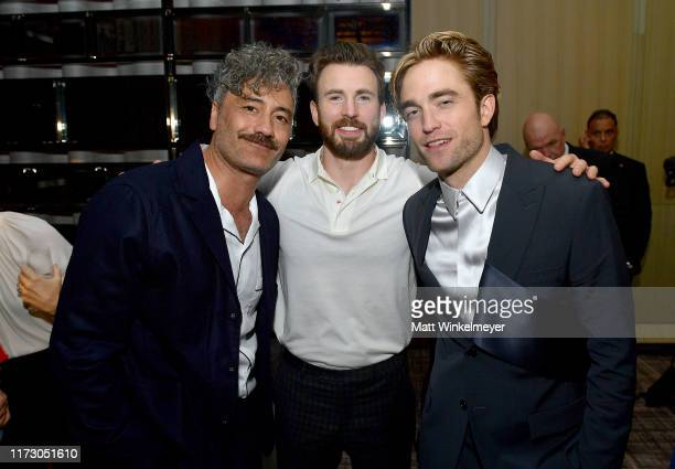 Taika Waititi, Chris Evans, and Robert Pattinson attend The Hollywood Foreign Press Association and The Hollywood Reporter party at the 2019 Toronto...
