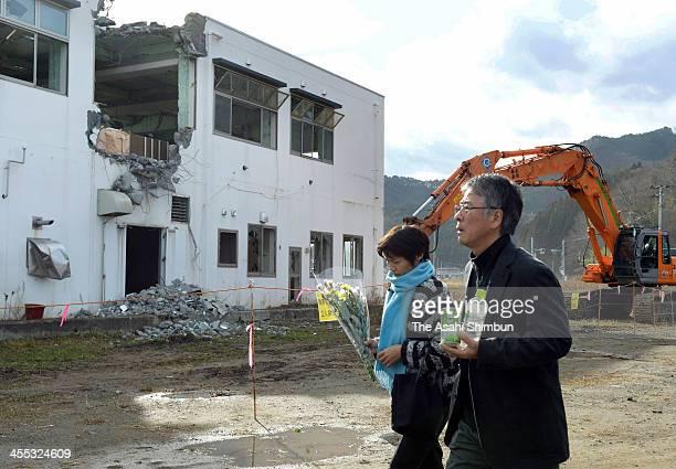 Taiki Terasawa and his wife Nakako visit the former Unosumai Area Disaster Prevention Center on December 11 2013 in Kamaishi Iwate Japan 200 people...