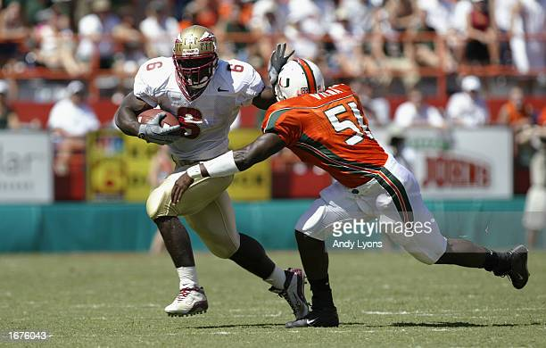 Tail back Greg Jones of Florida State carries the ball as he tries to elude linebacker Jonathan Vilma of Miami during the game on October 12 2002 at...